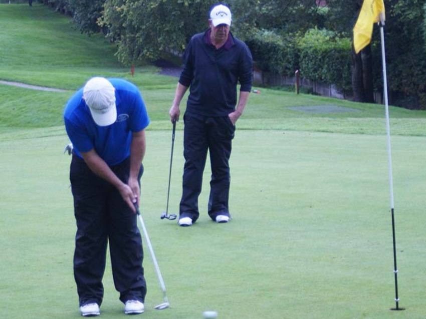 Phil Archer putts out under the watchful eye of MDGA Captain Gary Brown